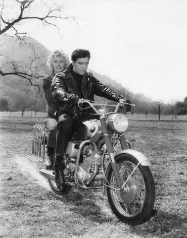 1964 Thousand Oaks, California Barbara Stanwyck and Elvis Presley ride a Honda in Roustabout