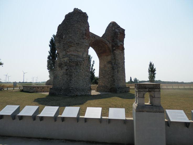 """Heidentor, Carnuntum. Ve starověku byla pevnost Carnuntum součástí římské provincie Pannonie. Oblast byla osídlena v druhé polovině 11. století a již ve 12. století obdržela obec práva trhů. Dějiny místa jsou stejně proměnlivé jako dějiny celého Rakouska. Ve 13. století již existovala """"Petronellská linie"""" rodu Liechtensteinského."""