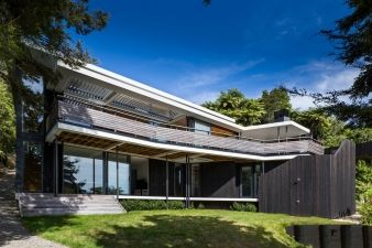 Dark vertical timber cladding and a soft grey roof help the house rest amongst the bush