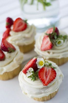 Cupcakes topped with strawberries and strawberry flowers
