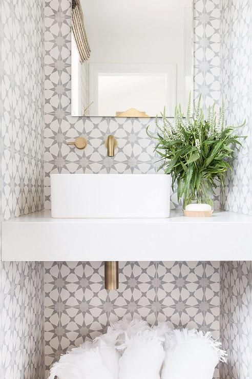 Alyssa Rosenheck - Amanda Barnes Interior Design - A gold trimmed vanity mirror hangs from a wall covered in  Cement Tile Shop Atlas Tiles and fitted with an antique brass wall mount faucet positioned over a white porcelain square sink fixed to a white floating vanity.