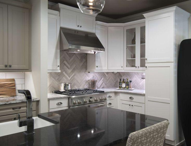 This kitchen in our design studio features our Wellborn cabinets in glacier, chenile white backsplash in a stunning herringbone pattern, and Cambria Edinborough island quartz countertop