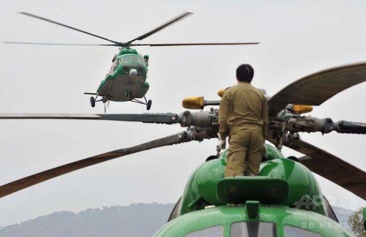 ラオスのボーリカムサイ県で、ヘリコプターの機内から立ち上がる軍兵士(2010年3月26日撮影)。(c)AFP/HOANG DINH Nam ▼29Jul2015AFP|ラオスで軍用ヘリ墜落、23人が行方不明 国営メディア http://www.afpbb.com/articles/-/3055886