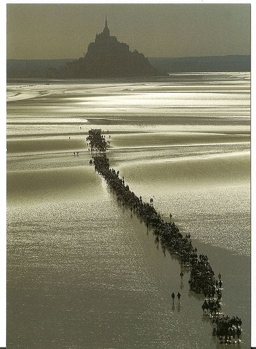 Mont St-Michel with pilgrims, off the coast of Avranches, Normandy, photo uncredited. The first monastery here was begun in the 8th century.
