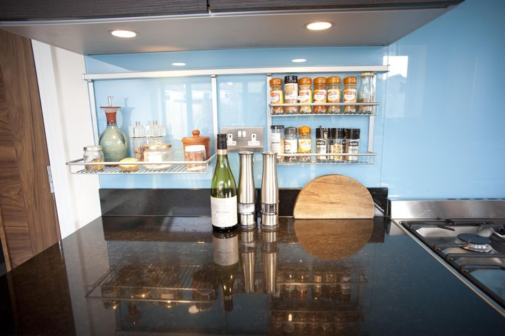 This Nolte kitchen features a combination of grey Manhattan Uni Metallic Kubanit on the base units, and the darker Nature Oak Mocha wall units, which both contrast beautifully with the striking blue glass splashbacks.