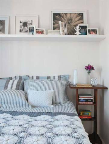 """Em função da cama de padrão king no quarto do casal, sobraram apenas 40 cm de largura de cada lado para os criados-mudos. """"Escolhi um móvel de cabeceira alto e estreito, com três níveis de apoio"""", fala a decoradora Maristela Gorayeb. Roupa de cama da Trousseau e almofadas da Coisas da Dóris. Sobre a prateleira, estão os quadros da Fast Frame e os porta-retratos da Tok & Stok e da Benedixt."""