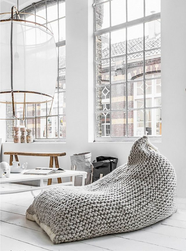 Loft living space with large windows, a paper lantern, and a large woven bean bag