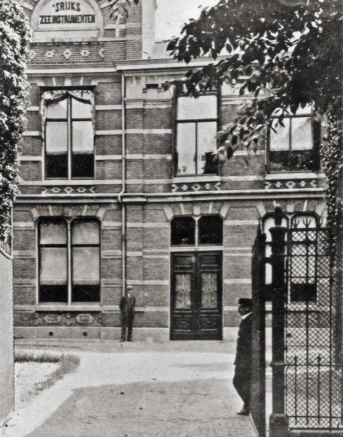 Hoofdingang van het gebouw van Verificatie van 's Rijks Zee-instrumenten aan de Oude Varkenmarkt te Leiden in 1914 met links de Adviseur-Verificateur ir. M.C.F.J. Cosijn en rechts bij het hek de bureeloppasser J.C. van der Breggen
