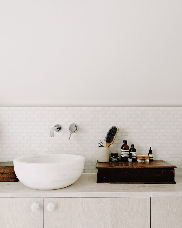 White Vessel Sink, With The Wall Mounted Faucet, White Tile And Cabinets,  With Wood Accents.