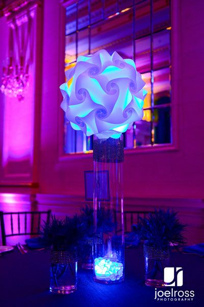 Blue table centerpiece. a jigsaw lamp lit in blue, surrounded by cylinders of blue thistle. Bar mitzvah decor