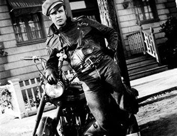 """Ένα από τα πρώτα κλασικά φιλμ για συμμορίες με μηχανόβιους, το ασπρόμαυρο """"The Wild One"""" προβλήθηκε το 1953 και ανέδειξε σε σταρ τον Marlon Brando. Ο Johnny Strabler, στο ρόλο ο Brando, είναι αρχηγός των"""