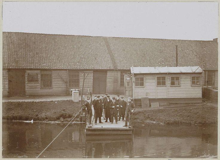 Anonymous | Mannen, vermoedelijk werknemers, staand op een aanlegsteiger bij een fabriekshal, Anonymous, c. 1900 - c. 1910 | Onderdeel van Familiealbum met onder meer foto's van Wijnhandel Kraaij & Co. Bordeaux-Amsterdam.