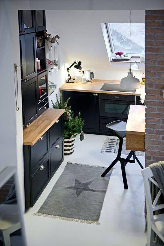 Aranżacja małej kuchni na poddaszu z czarnymi szafkami