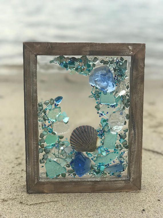 This is a handmade, one of a kind, sea glass/beach glass art piece. The photo represents the exact piece you will receive, please use the zoom feature to see all of the detail to make sure this style works for you. Sea glass and shells are secured with a resin casting. The frame is #seaglassart