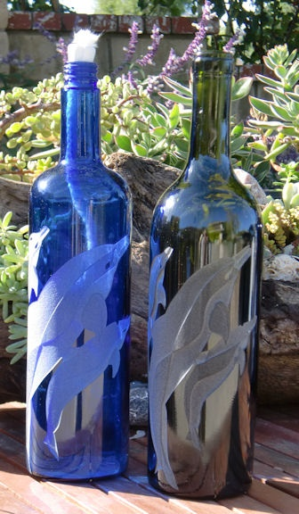 Dolphin design is carved / sandblasted onto wine bottles that transform into oil lamps.