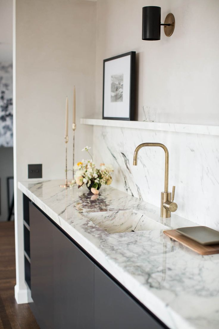 dark lower cabinets, marble worktop, brass tap, black sconce, picture ledge