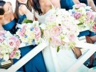 Complimented by her bridesmaids' unique bouquets, this bride carries a bouquet of white hydrangea, O'Hara garden roses,  white callas, astilbe, ranunculas, white Majolica roses, and Ornithogalum arabicum.  Floral design by  Soirée Floral . Photo by  Life Fusion Photography .