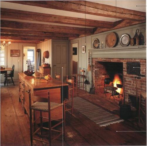 I like the paneling alongside the fireplace painted the same color as the mantle, exposed beams, and wide plank pine floors.