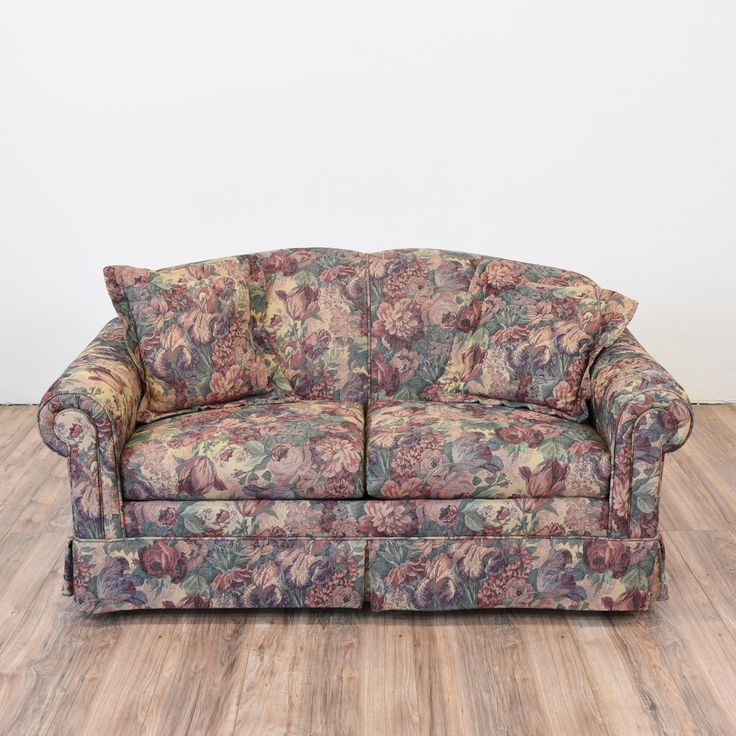 This loveseat is upholstered in a durable floral print fabric in a dark green, red, purple and beige. This colorful sofa is in great condition with a curved back and arms and simple skirt. Comfortable and eclectic sofa for a cottage style home!   #eclectic #sofas #loveseat #sandiegovintage #vintagefurniture