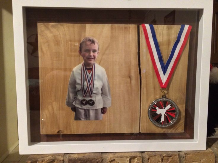 Grandson's picture and 1 medal mounted on the board he broke in his first karate tournament.
