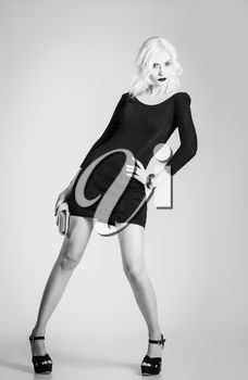 Studio fashion shot: beautiful girl in black dress with clutch in hand. Black and white