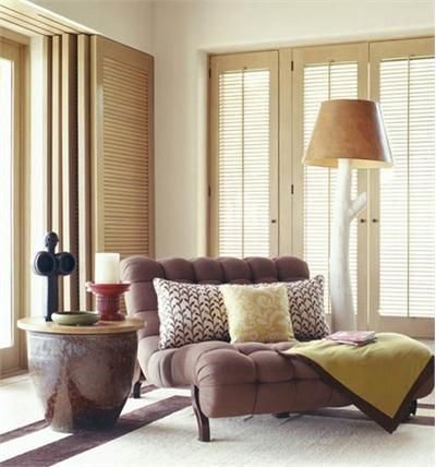 Trip Haenisch combines these elements in this transitional family room: branch floor lamp; brown and white area rug; brown lounge chair; custom window shutters; folding shutters; round end table; tufted lounge chair.