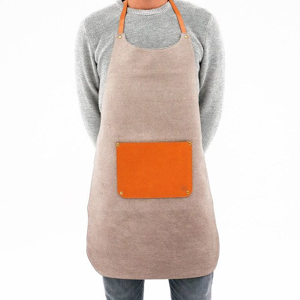 A hard-wearing grey canvas apron that is water-resistant and features a spacious vegetable-tanned leather front pocket.     Designed by La Portegna, handcrafted in Spain and available online from waremakers.com