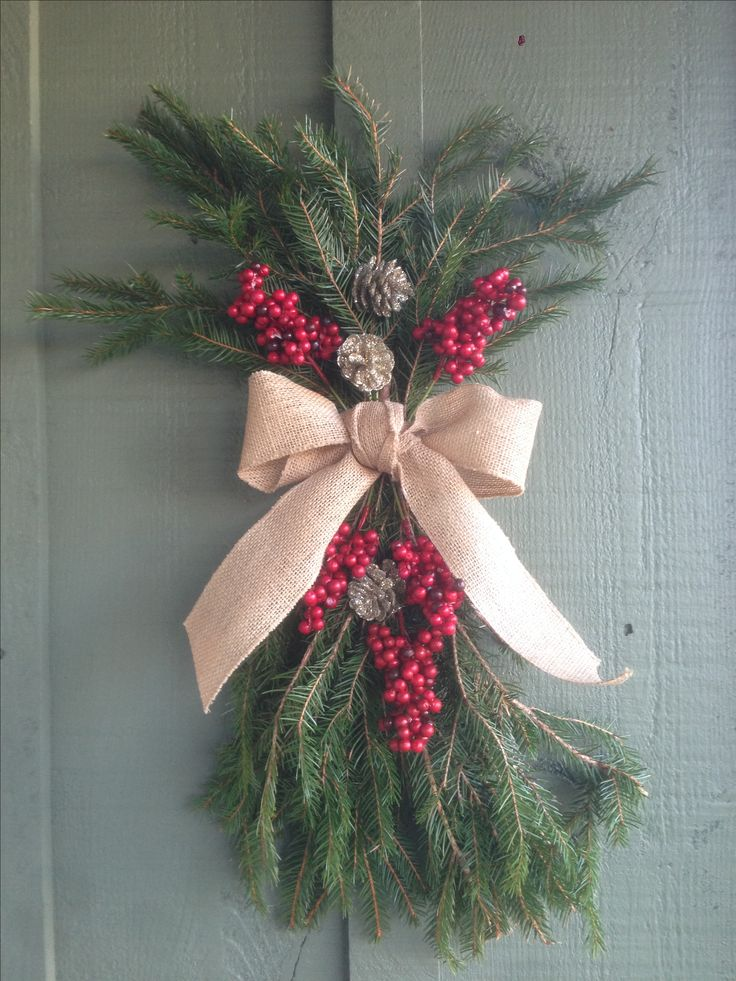 Christmas swag. Leftover branches trimmed from the Christmas tree, red berries and glitter pine cones from the dollar store, and a bow made from burlap ribbon.