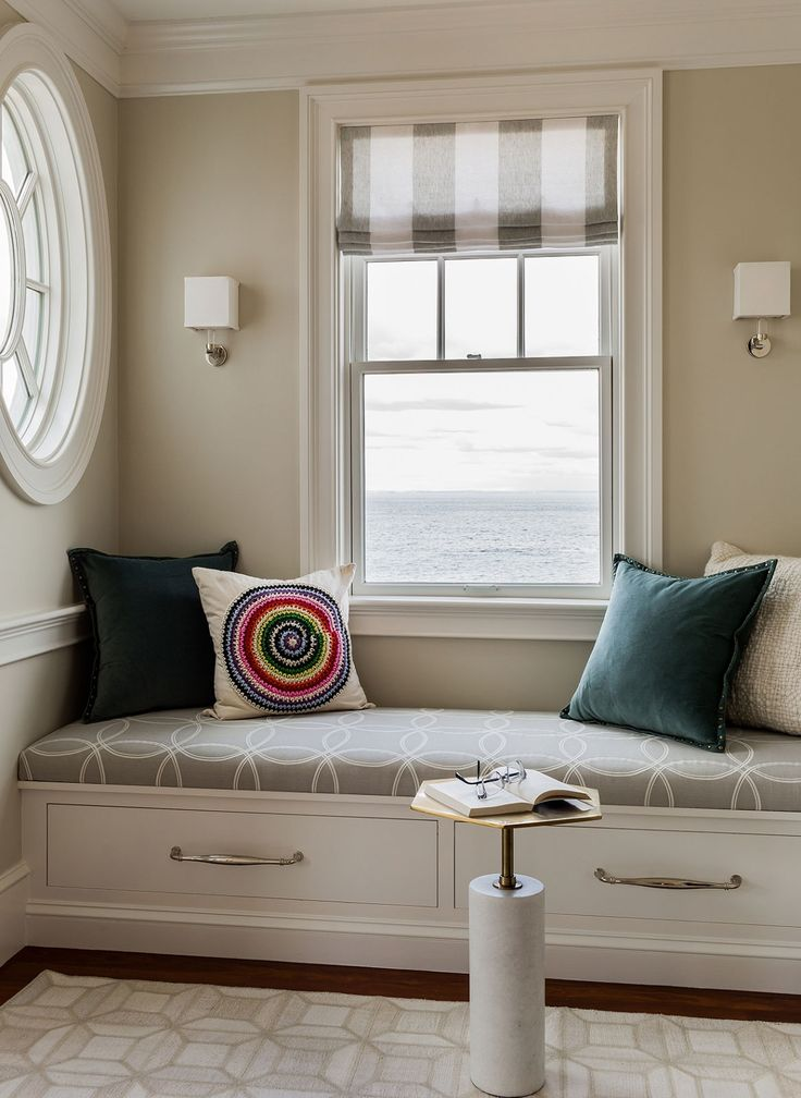 Bench seat under a window flanked with Geneva Sconces by Boyd Lighting. Interior design by Jennifer Palumbo.