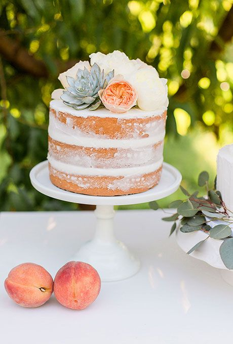 A one-tier naked wedding cake topped with fresh flowers and succulents, created by Candy Dunaway.