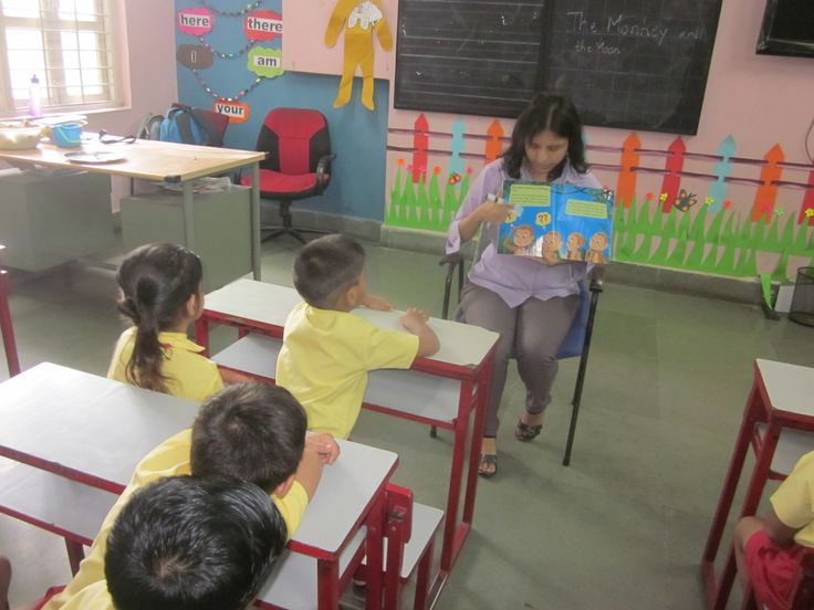 students of nursery listening to the story narrated by their teacher.