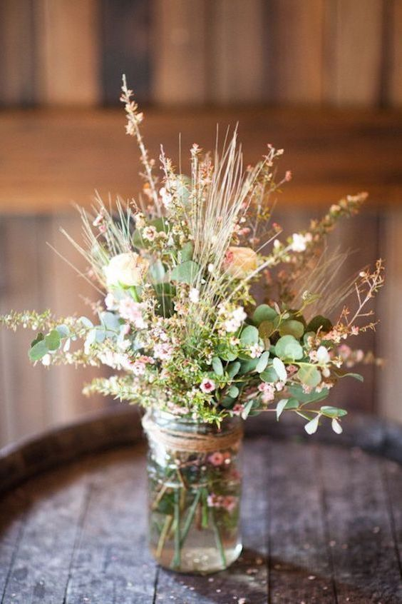Decora tu boda rústica con mason jars y una mezcla de flores salvajes y ramas de eucalipto. Tipos de bodas con los que combina: campestre, de jardín, urbana o temática personal.
