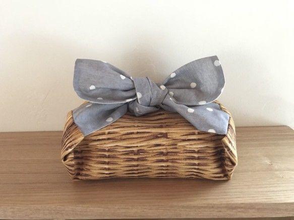 ちょっと変わったお弁当袋のようなお弁当包みです♪一風変わった形のお弁当袋(お弁当包み)に驚くかたも…⁉︎巾着袋のような形ではなく入れるところが筒抜け状態になった☆筒状☆のお弁当包みになっています。お弁当箱を筒状部分に入れたら両端が結び部分となります♪結びには丸い○タイプと三角△タイプがあります♪☆お手持ちのお弁当箱などの形よって柄の出方、形は画像と多少の違いが出ると思います。☆箸箱やカトラリーケースも一緒に包めますがその際はお弁当箱にプラスしてサイズを確認して下さいね♪***むすび丸タイプ筒状のお弁当袋***結びはサラリとした綿麻ローンのグレードットと裏地は生成りシーチング♪柔らかな雰囲気のドット柄…⚪︎⚪︎⚪︎♪筒状部分は本物のバスケットのようなコットンオックスプリントとの組み合わせです✨筒の中にポンっとしまって むすぶだけのシンプルだけど とっても姿が可愛い個性的なお弁当袋です♪画像は 容量500mlで 高さ5㎝、長さ13㎝、幅11㎝の容器を包んでいます♪ また形は違いますがスリムタイプの2段ランチボックス 容量350mlで…
