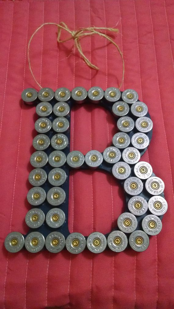This is an 8in wooden block letter accented with shotgun shells and twine hanger. Gold, silver or a variety of shells can be used. If you prefer