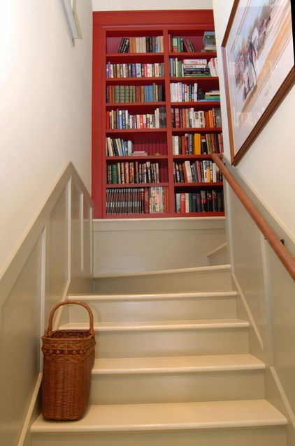 Shelves need only be as deep as your widest book's width, so you can make do with as little as 9 extra inches of depth. Using a contrasting wood or paint color punctuates this added landing feature.
