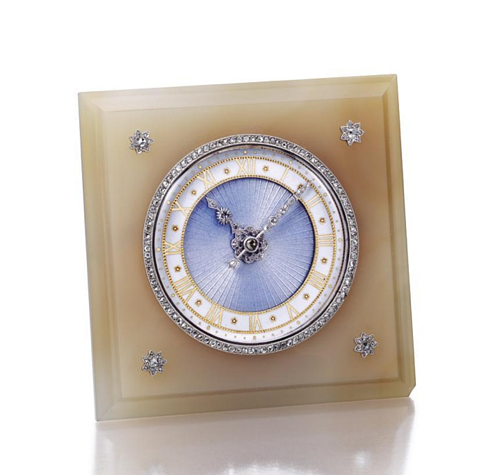 GOLD, AGATE AND DIAMOND DESK CLOCK, CARTIER, CIRCA 1925.  The circular dial applied with translucent pale blue enamel over a guilloché ground, white enamel chapter ring with gold Roman numerals, rose-cut diamond-set hands, the bezel also set with rose-cut diamonds, within a frame of taupe agate decorated at the corners with platinum and rose-cut diamond medallions, strut back, height 2 7/8 inches, case signed Cartier, movement by Cartier.