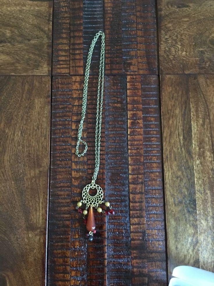 Bronze chain with a burnt orange teardrop on antique gold filigiri pendant