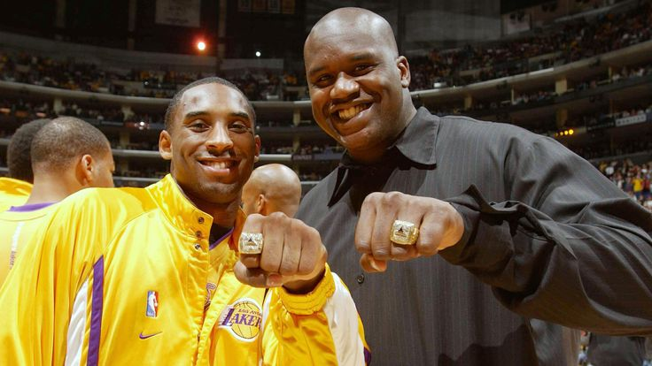 """""""The Kobe and Shaq Show."""" Lakers stars Kobe Bryant, left, and Shaquille O'Neal show off their 2002 NBA championship rings before a game against the San Antonio Spurs at Staples Center on Oct. 29, 2002. (Andrew D. Bernstein / Getty Images)"""