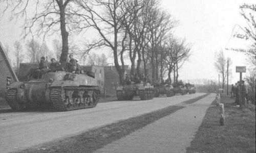 Troops of the Canadian Royal Hamilton Light Infantry aboard Kangaroo armored personnel carriers converted from Ram tanks, near Groningen, the Netherlands, 13 Apr 1945