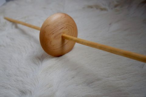 "Made of maple, the Navajo drop spindle is 76 cm/30″ long and has a weight 142 gr/5oz. This kind of spindle has been traditionally used by Navajo and Pueblo Indians to spin worsted wool for weaving their rugs, but it also works very well for fine wool. The Navajo spindle is called ""drop"" but it has to be supported on the floor. The spinner sits on the floor or in a chair with the bottom part of the shaft resting on the ground and the top part on the thigh and the spindle is rolled up the…"