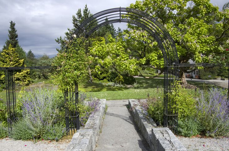 Beautiful arch entrance in a garden, VanDusen Botanical Garden. VanDusen Botanical Garden in Vancouver features a beautiful metal arch in its walkway entrance.