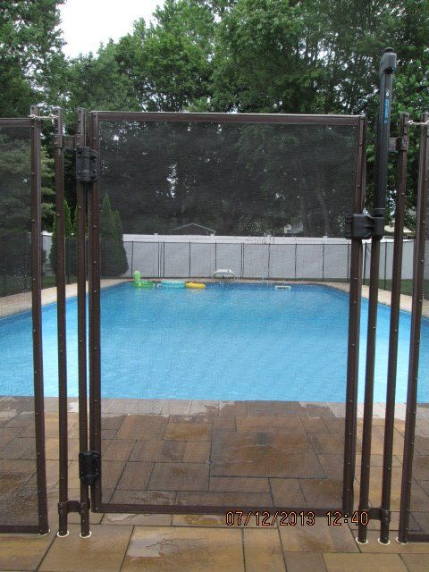 Brown self closing pool fence gate.