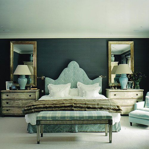 Elegant blue tone on tone bedroom design! Blue upholstered tufted headboard bed with gorgeous wood chest nightstands! The gold leaf mirrors & blue lamps really make this room! Love the monochromatic feel in this space!  Striped upholstered bench ottoman! Designer: Nicholas Haslam (http://www.nh-design.co.uk/)
