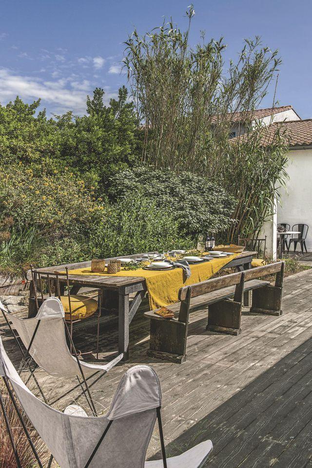 """Dans le patio privé, un grand drap Curry est déployé, et la table d'été s'anime d'instants gourmets. Mobilier vintage et bancs dénichés à la brocante Côté Jardin sur la place du Marché. Fauteuils """"AA"""" chinés. Assiettes, Jacqueline Morabito pour Galateo. Corbeilles, Best Before."""