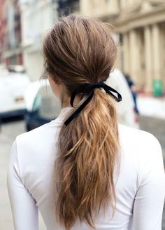 Tie a ribbon in a bow around a pony tail for a simple and easy hair trend