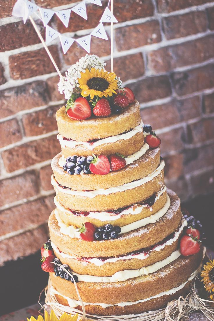 Rustic naked wedding cake. Fresh fruit, sunflowers and bunting!