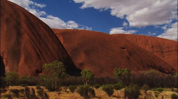 この写真はどこでしょうか? まっ赤な砂岩の岩山…あの「世界の中心で、愛をさけぶ」で舞台になったエアーズロックです。先住民アボリジニは<ウルル>と呼びます。