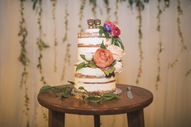 A semi naked wedding cake done up with bold colours#vietnambeachweddings #hoianeventsweddings #rusticwedding #beachwedding #destinationwedding