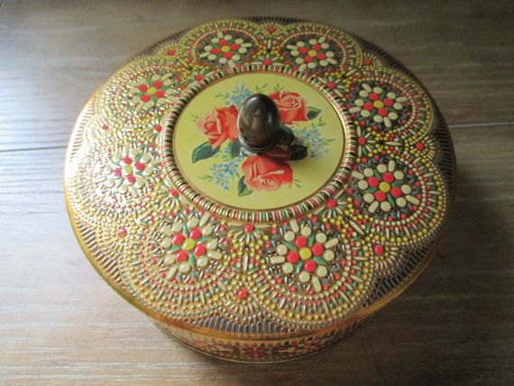 "Vibrant pink, red, gold, green and blue colors adorn this tin in an edwardian floral pattern. The pattern is further enhanced by its raised relief design.   Measures: 6 3/4"" Diameter x 2 1/2"" High (3 1/2"" High including knob).  This tin is in excellent vintage condition."