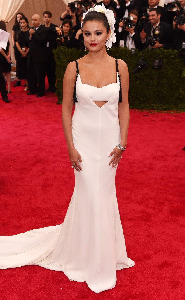 2015 Met Gala: Selena Gomez is wearing a white sleeveless Vera Wang gown with a cutout detail on the bodice and black straps. Selena is beautiful in white! The head piece adds interest.